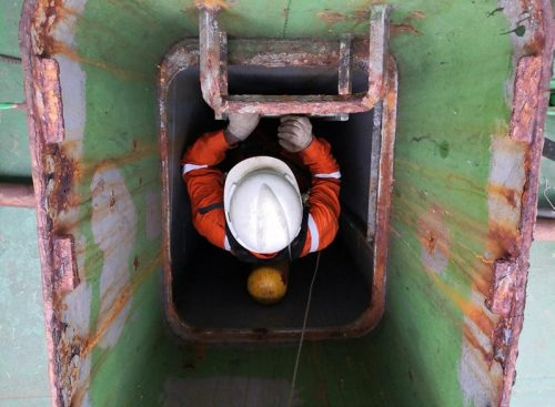 Rescuer equipped with breathing apparatus descending into a shipboard closed space.